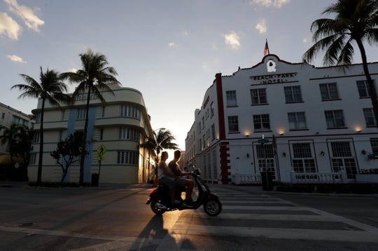 Two people on a scooter ride through the normally bustling streets of the Art Deco District as the sun sets, Wednesday, March 25, 2020, in Miami Beach, Florida's famed South Beach.