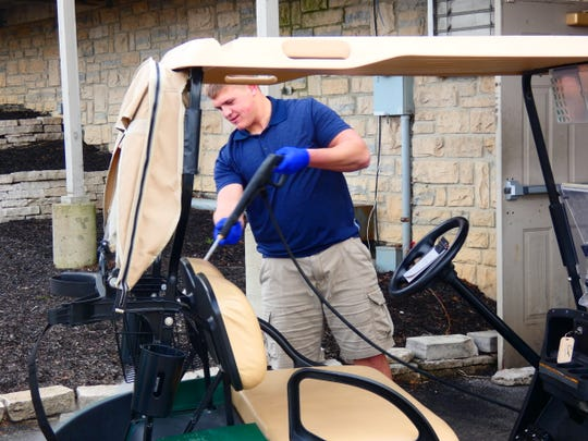 Watkins Memorial senior Tony Calovini cleans golf carts Thursday at Cumberland Trail. Following the Licking County Health Department's ruling Friday, courses can remain open as long as carts are not used and registration is done online.