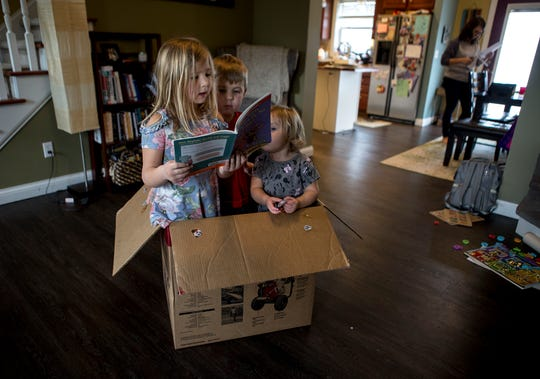 Lilli Morgan, 6, reads to her brother Isaac, 5, and sister Naomi, 2, in a box their parents saved for them to use while they are home from school due to the novel coronavirus. Last week was the first week of school closures in Ohio and parents have been scrambling for ways to homeschool their children and keep them engaged in learning. Isaac was fulfilling one of his school requirements by having a family member read to him.
