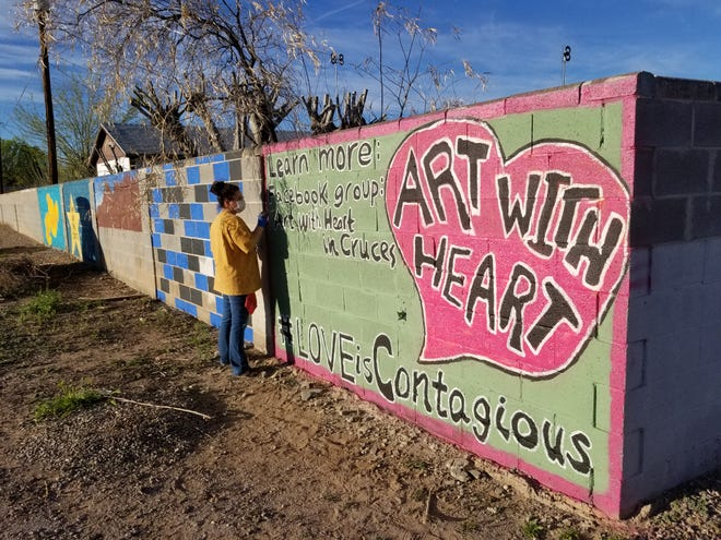Las Cruces residents gathered Saturday, March 21, 2002, to help paint over racist tags left on Wanda Saip Ray's backyard wall.