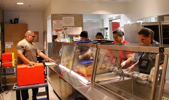 The Alamogordo Senior Center staff prepares meals for seniors March 26.