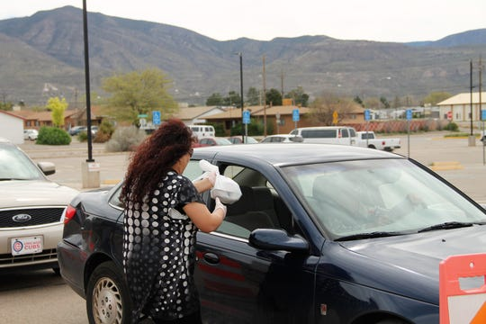 Alamogordo Senior Center Manager Magdalena Morales gives a meal to a senior citizen during curbside pick up March 26.