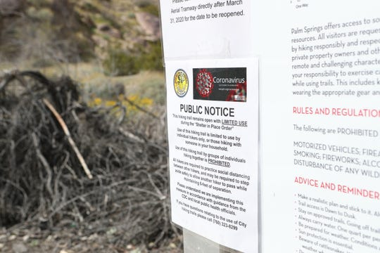 A public notice from the City of Palm Springs informs hikers on the North Lykken Trailhead that they need to allow six feet distance when passing other hikers in Palm Springs, Calif., on Wednesday, March 25, 2020.