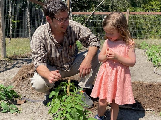 """Pensacola area nurse Dallas Peel and daughter Aspen, 3, check out some tomato plants in their garden in Lillian, Ala. Peel agrees that gardening is good way to practice """"social distancing"""" in light of coronavirus."""