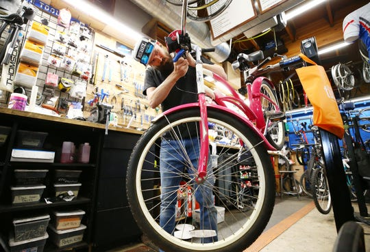 Dylan Shea repairs a bicycle at Grey Matter Family Bicycle Shop on March 25, 2020, in Phoenix. Staff members say they are having trouble keeping up with demand for repairs as more people turn to cycling to stay fit and get outdoors during the coronavirus pandemic.