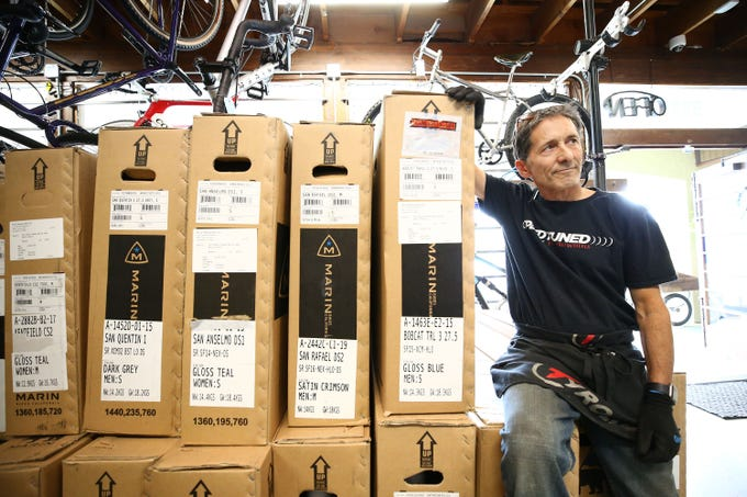 Mike Stransky, a salesman at Grey Matter Family Bike Shop, handles a new shipment of bicycles. The Phoenix store has seen a jump in business as people turn to cycling during the coronavirus pandemic.