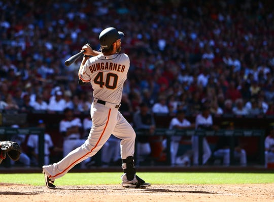 San Francisco Giants pitcher Madison Bumgarner hits a solo home run in the seventh inning against the Arizona Diamondbacks during opening day at Chase Field in 2017.
