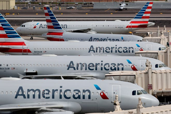 American Airlines jets sit idly at their gates as a jet arrives Wednesday, March 25, 2020, at Sky Harbor International Airport in Phoenix. Airlines in the U.S. are starting to idle planes due to a sharp drop in bookings caused by the COVID-19 and coronavirus outbreak.