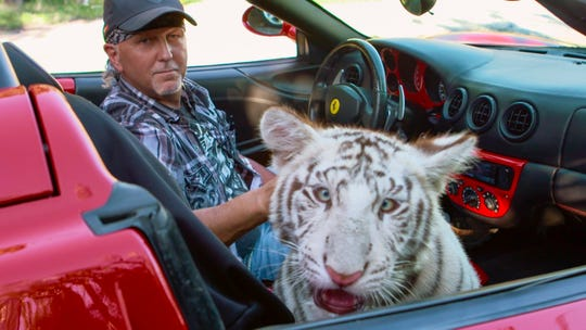 Jeff Lowe, one of a cast of colorful characters in the Netflix documentary 'Tiger King,' rides with one of the big cats.
