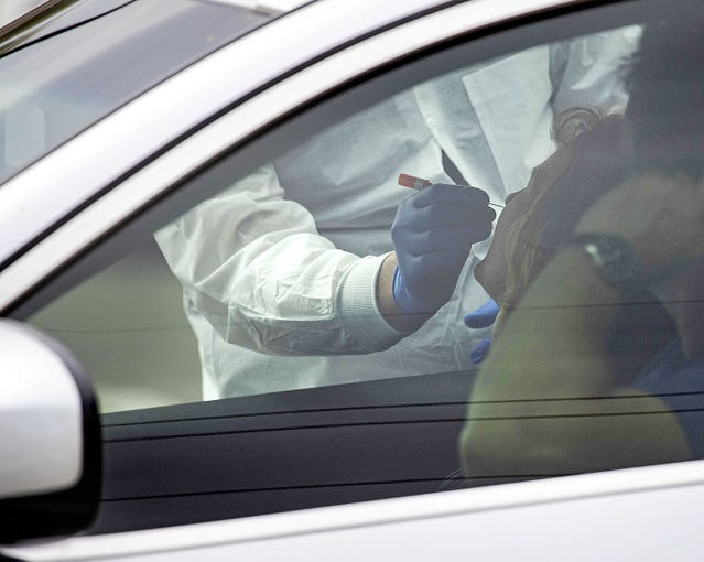 Adam Hansen, a doctor from Redirect Health, takes a swab from a patient in a drive-thru to test for flu and coronavirus on March 25, 2020.  Medicare and some insurance plans will cover the testing (with normal co-pays and deductibles) or there is a $49 self-pay option. Experts say it's important to get a test inside the first 48 hours of symptoms starting.