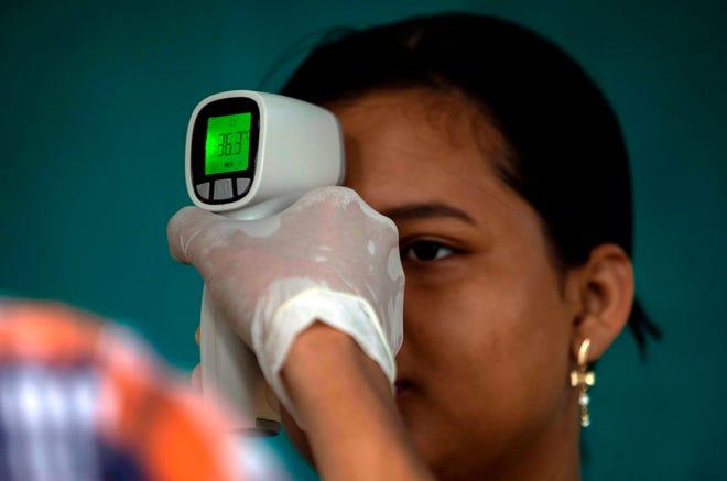 Una mujer se toma la temperatura, en un punto de inspeccion anti-coronavirus en Guatemala.
