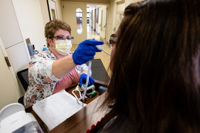 Lake Huron Medical Center Senior Services and Volunteer Coordinatory Rosemary Hunger screens a hospital employee as she enters Thursday, March 26, 2020. As a precaution, every person who enters the hospital is pre-screened for symptoms of coronavirus.