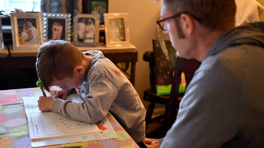 Nolan Matseur, 6, works on a number tracing worksheet under the watchful eye of his father Andrew as the Mount Wolf family have had to juggle homeschooling during the pandemic shutdown. Wednesday, March 25, 2020. John A. Pavoncello photo