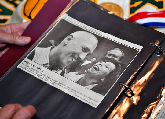 Former York Catholic boys' basketball coach Mike Keesey pauses on one of his favorite photos of him, his wife Peggy Keesey, right, and his uncle Frank Benkert, back right, while flipping through a photo album at his home in West Manchester Township, Thursday, March 26, 2020. Dawn J. Sagert photo