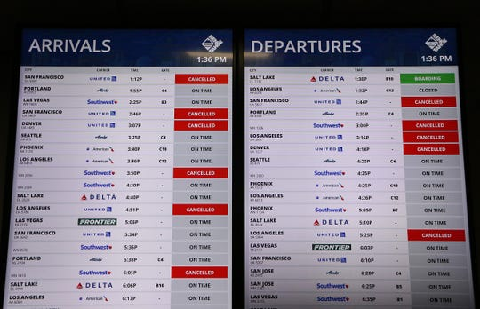 Multiple cancellations are seen on a flight board at the Reno-Tahoe International Airport on March 26, 2020.