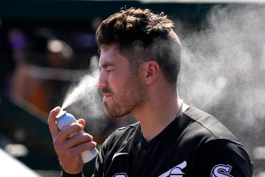Chicago White Sox infielder Danny Mendick of Pittsford sprays sun tan lotion on his face before a spring training game against the Los Angeles Dodgers on Feb. 24, 2020. Spring training has been suspended due to the coronavirus, but Mendick is still able to work out at the White Sox facility.