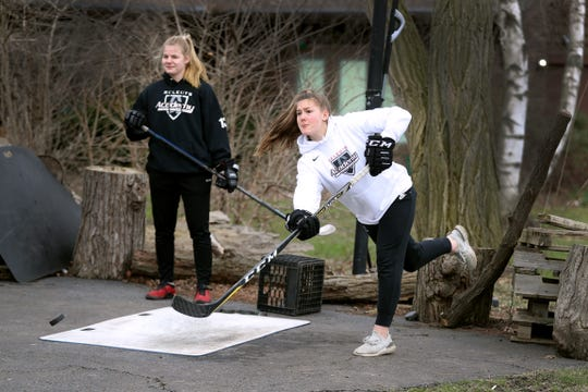 Haley Winn (white) and Nina Christof , both part of the Bishop Kearney Selects hockey program, shoot pucks in Haley's driveway during a study break.  Nina is from Germany but could not get home after the coronavirus shutdown.  She is staying with the Winn family in Penfield as her parents try to find a way to get her home.
