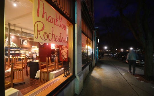 A sign thanking the people of Rochester, hangs in the window of Magnolias restaurant on a near empty Park Ave.