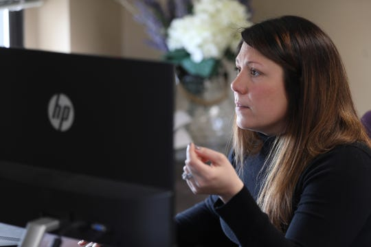 Sarah Wesley of Wesley, Clark  & Bates LLC checks emails at her office in downtown Rochester on March 26, 2020.  She has been dealing with issues related to co-parenting during coronavirus pandemic.