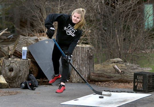 Nina Christof ,  who is part of the Bishop Kearney Selects hockey program, shoot pucks in friend and teammate Haley Winn's driveway during a study break.  Nina is from Germany but could not get home after the coronavirus shutdown.  She is staying with the Winn family in Penfield as her parents try to find a way to get her home.