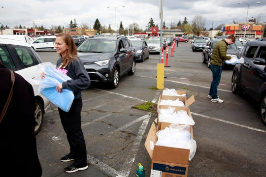 Amelia Hunt (left) and Bryce Petersen of Salem Health give mask-making kits to drivers during a kit pick-up event in Salem, Oregon, on Thursday, March 26, 2020. Salem Health has requested community help sewing nearly 10,000 masks for local health care workers.