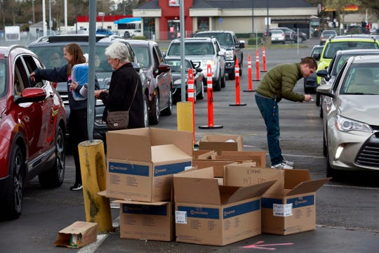 Amelia Hunt (left) and Bryce Petersen of Salem Health pass out mask-making kits to drivers during a kit pick-up event in Salem, Oregon, on Thursday, March 26, 2020. Salem Health has requested community help sewing nearly 10,000 masks for local health care workers.
