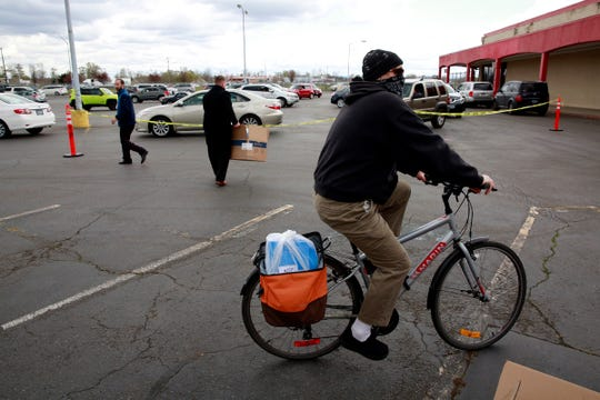 A bicyclist pedals away with a mask-making kit during a distribution event in Salem, Oregon, on Thursday, March 26, 2020.