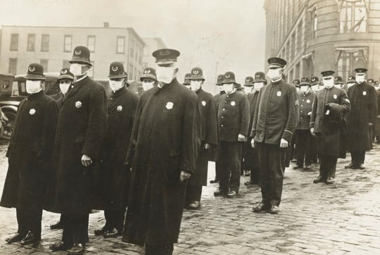 Seattle police officers wear masks during the influenza epidemic made by the local chapter of the American Red Cross in this National Archives photo dated December 1918.