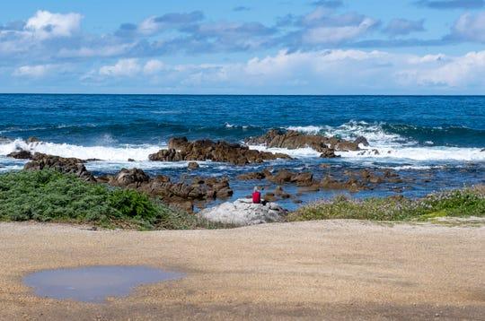 A woman sits on a large rock near Asilomar beach on March 25, 2020.
