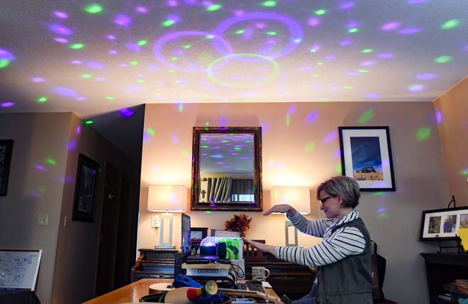 "Sara Southwood, music teacher at Rosa Parks Elementary School, uses a ""disco light"" while recording a lesson on movement and rhythm for kindergarten students on Thursday morning, March 26, while working remotely at her home in Sioux Falls."