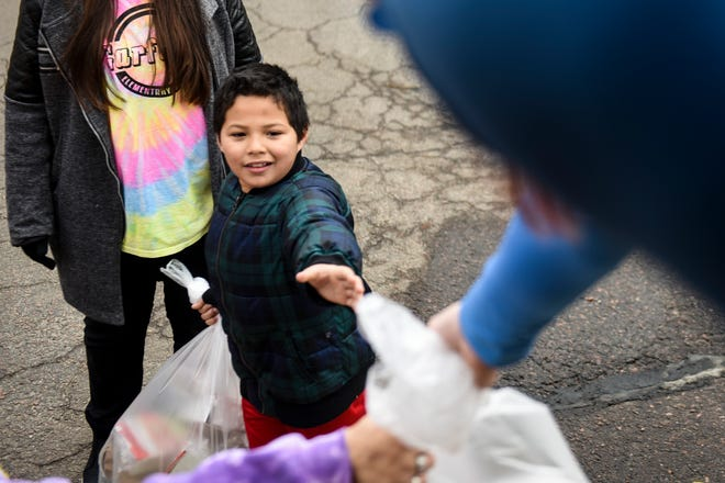 Garfield Elementary School fourth grader Eli Turcios picks up a school lunch on Thursday, March 26, 2020 in Sioux Falls. The Sioux Falls School District has suspended classes due to the coronavirus but are working with students to provide food and supplies.