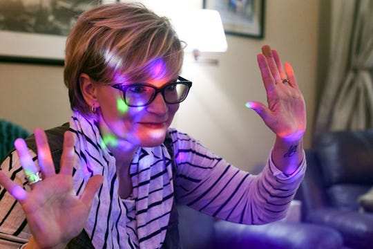 """Sara Southwood, music teacher at Rosa Parks Elementary School, uses a """"disco light"""" while recording a lesson on movement and rhythm for kindergarten students on Thursday morning, March 26, while working remotely at her home in Sioux Falls."""
