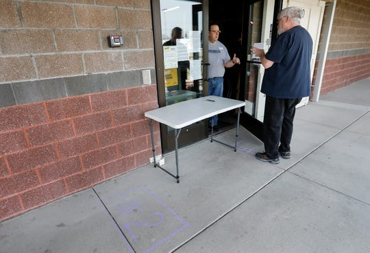 Don Harvey, right, talks with Cherokee Firearms manager Seth Gaines on Thursday. The store was seeing most customers at the door and only allowing one customer to enter if necessary.