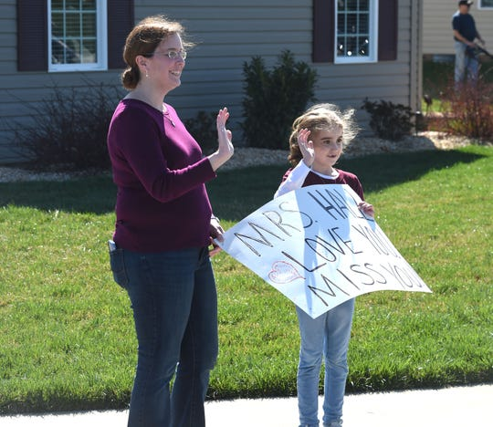 Averi Harris and her mom wait for the Cougar Paw Parade Thursday. Staff of Stuarts Draft Elementary School drove through area neighborhoods, waving to students who are now out of school for the year.