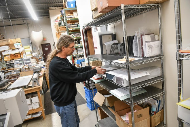 Ron Edelbrock looks through jobs to be completed on a shelf in the work area Wednesday, March 25, 2020, at Benton Trophy & Awards in Sauk Rapids. Edelbrock said that the shelf would normally be full to overflowing this time of year.