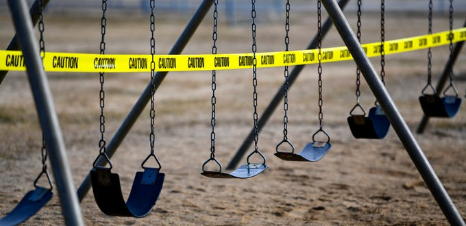Caution tape is posted on playground equipment as a precaution against the spread of COVID-19 Thursday, March 26, 2020, in St. Joseph.