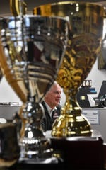 Owner Marty Heine is framed while trophies while talking about his business at All Star Trophy & Awards Wednesday, March 25, 2020, in St. Cloud.