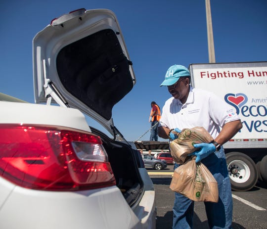 City Commissioner Curtis Richardson along with other volunteers, loads cars with bags of food during a food distribution event organized by Second Harvest of the Big Bend in the parking lot of the Tucker Civic Center, Thursday, March 26, 2020.