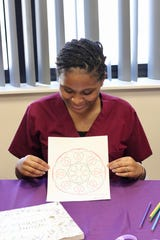 Sammi Washington, patient care assistant at TMH, takes a stress reducing break to color a mandala from the Code Lavender cart.