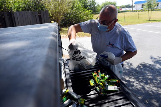 David Long fills a grocery bag with food, water, hand sanitizer and antibacterial wipes on Wednesday, March 25, 2020, as he and his wife, Kelly Long, go on a welfare check of people in a homeless camp off State Road 60 in Indian River County. The Longs are the directors of Angels of Hope, an outreach ministry based in Fort Pierce that helps the homeless in Martin, St. Lucie, Indian River and southern Brevard counties.