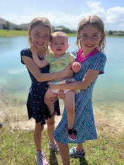 (From left) Ryley, 8, Layna, 1, and Kaley, 8, daughters of TCPalm Editor Adam Neal, pause for a photo during a walk around a neighborhood lake on March 22, 2020.