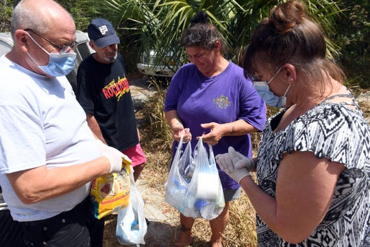 """David and Kelly Long deliver care packages of food, water, hand sanitizer and antibacterial wipes to a homeless camp on Wednesday, March 25, 2020, in Indian River County. """"I have to tell you about coronavirus,"""" Kelly Long said to the couple through a face mask. """"Try and keep your distance from other people and be sure to completely clean your hands."""""""