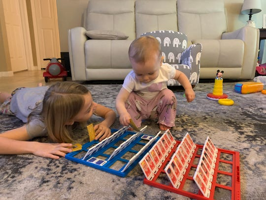 Kaley, 8, plays a game with Layna, 1, as their parents Adam and Michelle Neal (not pictured) work from home during the COVID-19 pandemic on March 15, 2020.