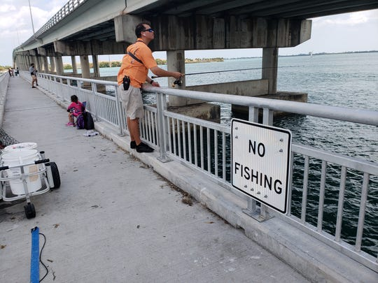 No Fishing signs are being ignored on the South Bridge catwalk in Fort Pierce, and that's ok.