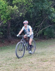 Jessica Ventura of Jupiter heads into the woods at Halpatiokee Park on one of the bike trails there Thursday.