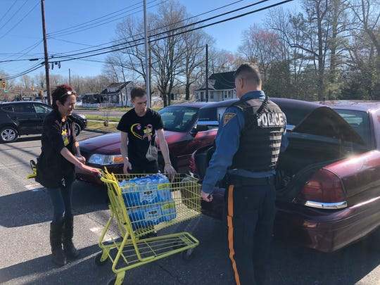 Dollar General manager Sandy Bowen and assistant manager, Chris Mazzoni, of the Main Road store, help Officer Felipe Laboy load  bottled water into his police vehicle. It was part of a larger donation the store management purchased for the first-responders with the pay bonuses they received.  March 26, 2020 .