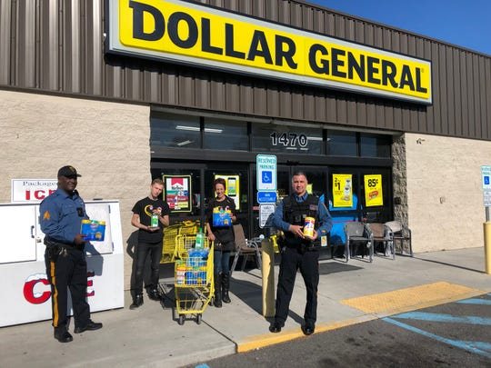 Dollar General manager Sandy Bowen and assistant manager, Chris Mazzoni, of the Main Road store, used their bonus pay to purchase bottled water and hand sanitizers for Vineland Police Department.  Sgt. Shane Harris (left) and Officer Felipe Laboy stopped by March 26, 2020 for a curbside pickup.