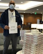 Bill and Hillary Clinton had pizza delivered to the staff at White Plains Hospital on March 25, 2020. Derron Hogg, navigator with the hospital's Compass Program, holds a note from the Clintons next to the delivered pizzas.