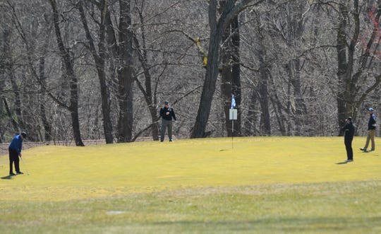 A foursome practices social distancing on the first green at Mohansic Golf Course in Yorktown Heights on March 26, 2020. Back on the tee, four golfers waiting to begin their round were standing close enough to shake hands.