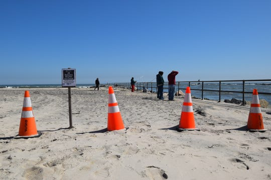 A sign and orange cones saying beach access is off-limits aren't heeded by all. Unless stricter local measures are in place, beaches can still be used for fishing and exercise activities.